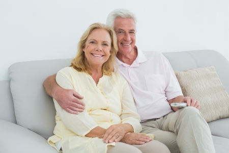 Portrait of a relaxed happy senior couple with remote control sitting on sofa in a house photo