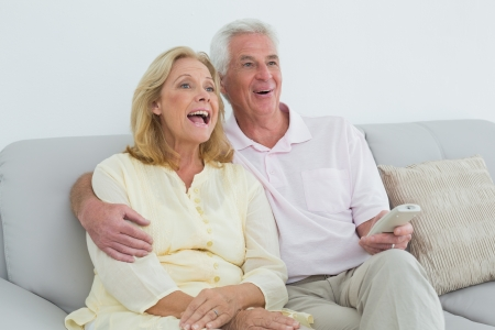 Relaxed cheerful senior couple with remote control sitting on sofa in a house photo