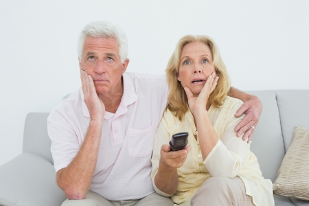 changing channels: Relaxed shocked senior couple watching television in a house