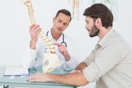 Männlich Arzt Erläuterung der Wirbelsäule zu einem Patienten in Arztpraxis