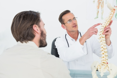 Male doctor explaining the spine to a patient in medical office photo