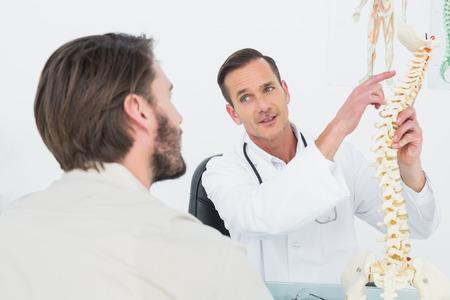 Mannelijke arts de wervelkolom aan een patiënt die medisch kantoor