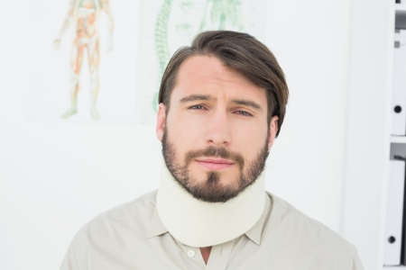 Portrait of a young man suffering from neck pain in the medical office photo
