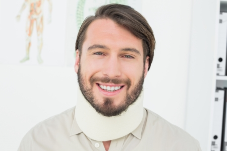 Portrait of a smiling young man wearing surgical collar in the medical office photo