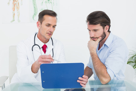Male doctor discussing reports with patient at desk in medical office 写真素材