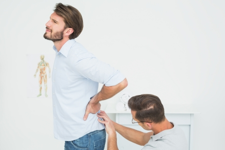 Side view of a male physiotherapist examining mans back in the medical office photo