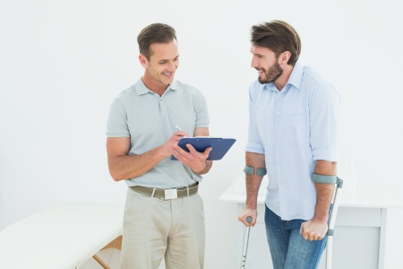 Male therapist discussing reports with a disabled patient in the medical office Stock Photo
