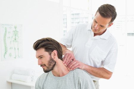 relax massage: Male therapist massaging a young mans neck in the medical office