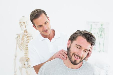Man chiropractor doet nek aanpassing in de medische kantoor