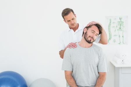 Male chiropractor doing neck adjustment in the medical office Фото со стока - 25506354