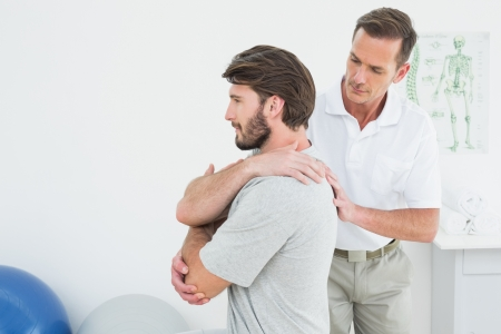 Male physiotherapist examining a young man in the medical office