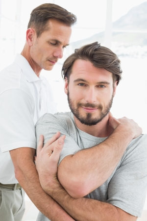 Male physiotherapist examining a young man in the medical office photo
