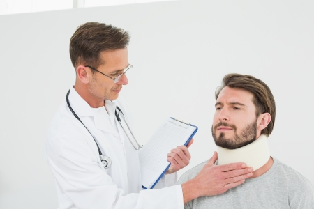 sprained: Male doctor examining a patients sprained neck over white background