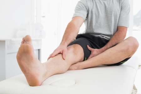 Low section of a young man with his hands on a painful leg while sitting on examination table photo