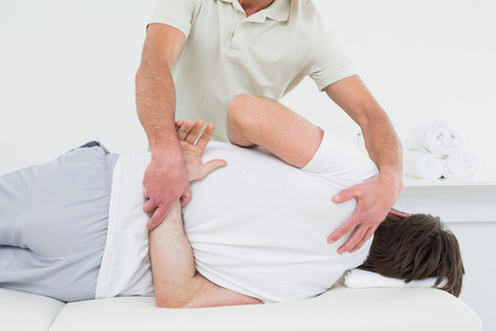 Male physiotherapist examining man's back in the medical office photo