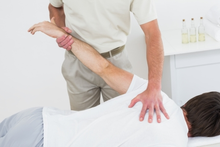 Male physiotherapist stretching a young mans hand in the medical office photo