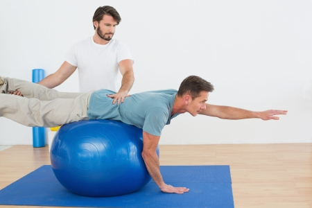 Physical therapist assisting young man with yoga ball in the gym at hospital Фото со стока - 25506423