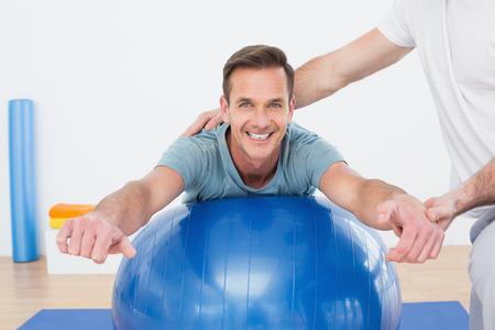 Physiotherapeut Unterstützung junger Mann mit Yoga-Ball in der Turnhalle im Krankenhaus Lizenzfreie Bilder