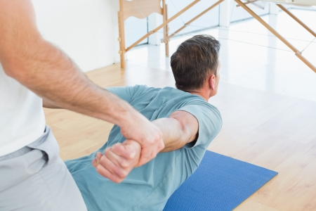 physical therapist: Physical therapist assisting young man with stretching exercises in the gym hospital Stock Photo