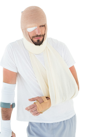 Young man with head tied up in bandage and broken hand over  white background Stock Photo