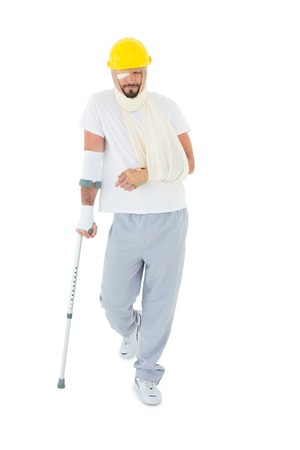 Full length of a young man in hard hat with broken hand and crutch over  white background photo