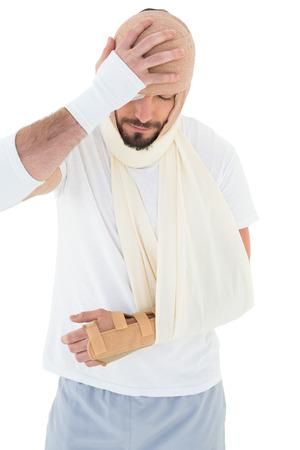 Junger Mann mit Kopf in Verband gebunden und gebrochenen Hand auf weißem Hintergrund