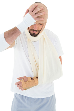 Young man with head tied up in bandage and broken hand over  white background photo