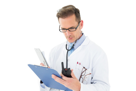 Serious doctor reading reports over white background  photo