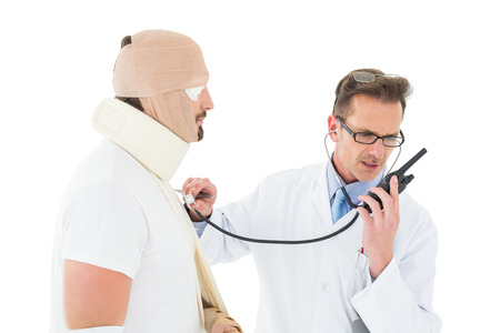 Side view of a doctor auscultating a patient tied up in bandage with stethoscope over  white background photo