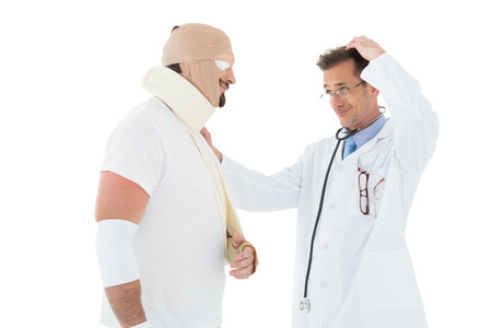 Side view of a doctor looking at patient tied up in bandage over  white background photo