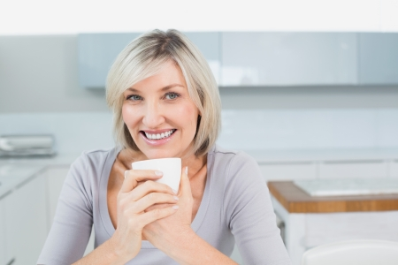 Close-up portrait of a smiling casual young woman with coffee cup in the kitchen at home photo