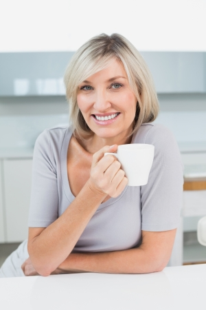Portrait of a smiling casual young woman with coffee cup in the kitchen at home photo