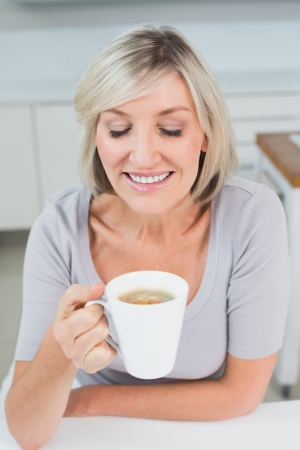 Close-up of a casual young woman drinking coffee in the kitchen at home photo