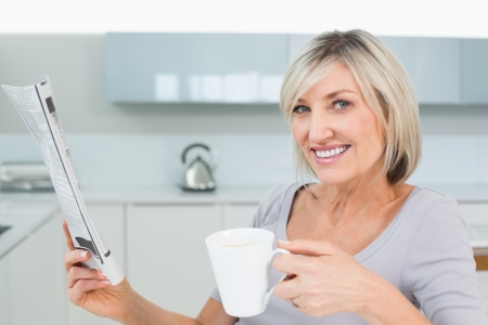 Portrait of a smiling young woman with coffee cup and newspaper in the kitchen at home photo
