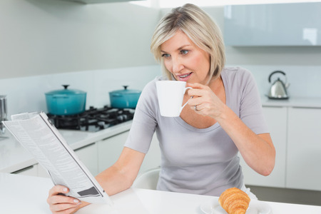 Casual young woman drinking coffee while reading newspaper in the kitchen at home photo