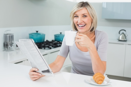 Portrait of a happy young woman with coffee cup and newspaper in the kitchen at home photo