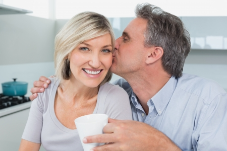 Man kissing a happy woman's cheek in the kitchen at home photo