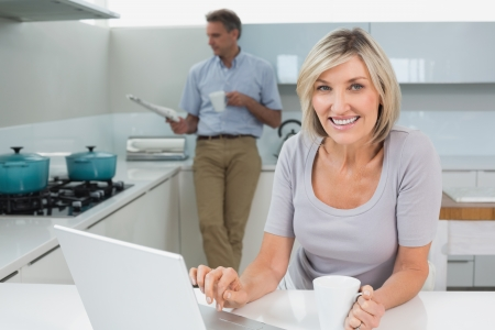 Woman using laptop while man reading newspaper in the kitchen at home photo