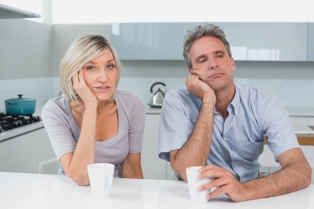 Portrait of a bored couple sitting with coffee cups in the kitchen at home photo