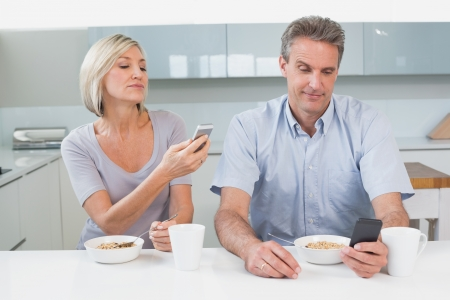 Couple reading text messages while having breakfast in the kitchen at home photo
