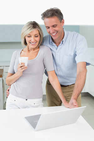 Happy casual couple looking at laptop in the kitchen at home photo