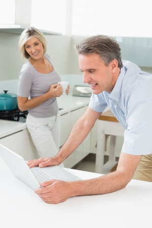 Man using laptop while woman standing in background at the kitchen photo