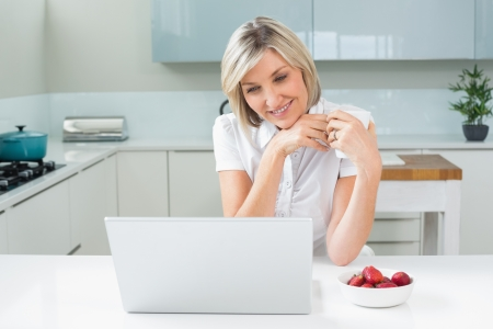Casual happy woman with coffee cup looking at laptop in the kitchen at home photo