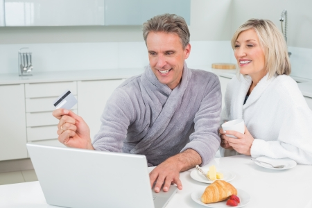 Happy couple in bathrobes doing online shopping in the kitchen at home photo
