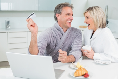 Cheerful couple in bathrobes doing online shopping in the kitchen at home photo