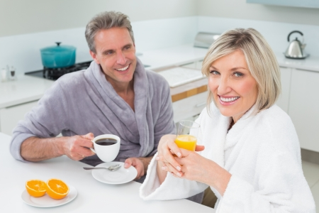 Happy couple in bathrobes having breakfast in the kitchen at home photo