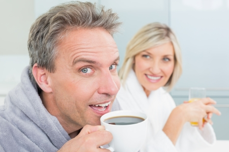 Close-up portrait of a happy couple in bathrobes with coffee cup and juice in the kitchen at home photo