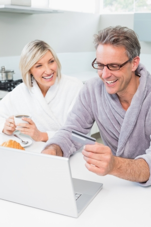 Couple in bathrobes using laptop in the kitchen at home photo