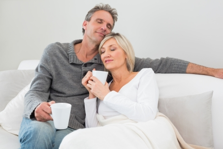 Relaxed man and woman with coffee cups in the living room at home photo