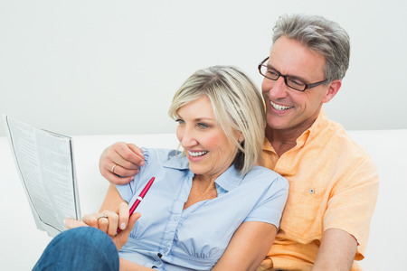Happy man and woman doing the newspaper crossword puzzle in the living room at home photo
